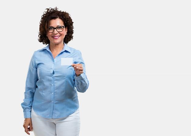 Среднего возраста женщина улыбается уверенно, предлагая визитную карточку, имеет процветающий бизнес, скопируйте пространство, чтобы написать все, что вы хотите