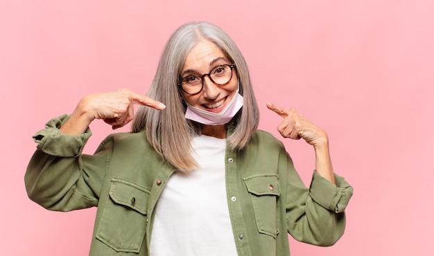 Женщина средних лет уверенно улыбается, указывая на собственную широкую улыбку, позитивное, расслабленное, удовлетворенное отношение