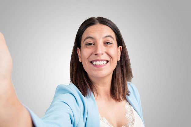 Middle aged woman smiling and happy, taking a selfie, holding the camera