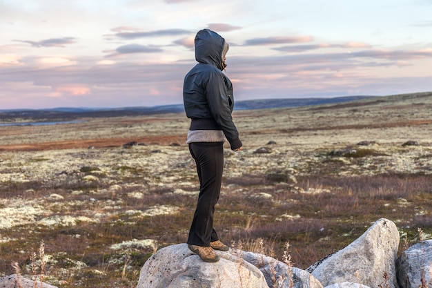 A middle-aged woman standing on the big stone in the tundra, travel concept