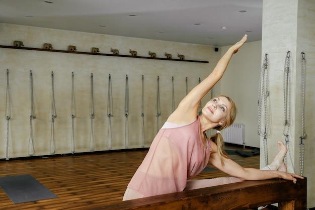 Женщина средних лет растягивает ноги на деревянной балке в тренажерном зале перед занятиями йогой