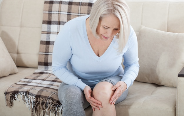 Middle-aged woman suffering from pain in leg at home, closeup.