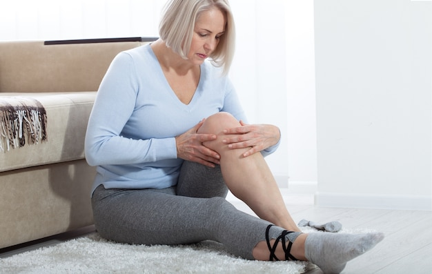 Middle-aged woman suffering from pain in leg at home.