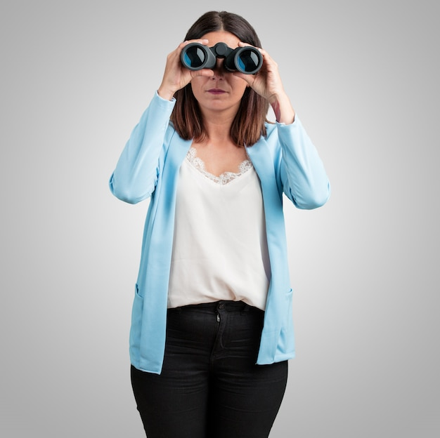 Middle aged woman surprised and amazed, looking with binoculars in the distance