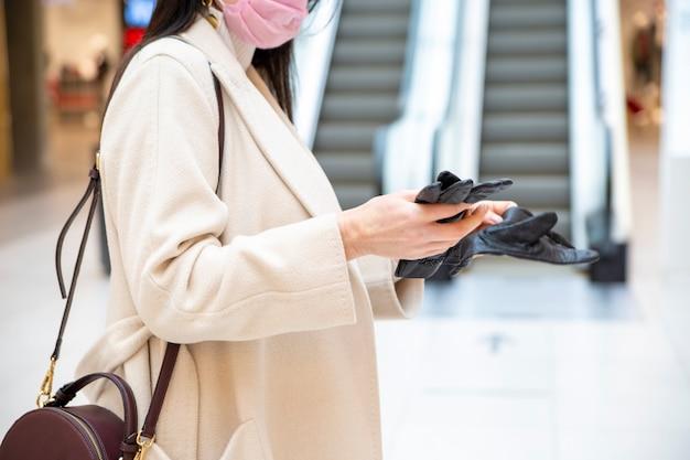 중년 여성은 에스컬레이터를 배경으로 쇼핑몰에서 장갑을 벗습니다. 얼굴이 없는