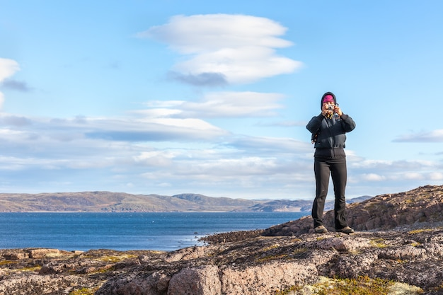 A middle-aged woman taking pictures standing on the rock