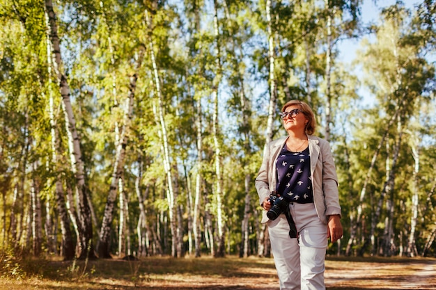 Middle-aged woman taking pictures using camera in autumn forest. senior woman walking