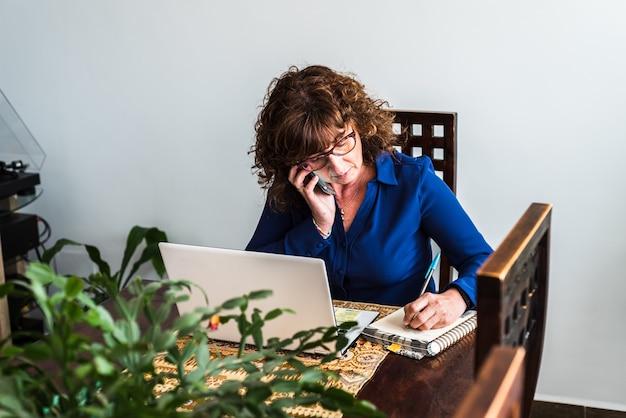 그녀의 휴대 전화로 이야기하고 그녀의 거실에서 일하는 중년 여성
