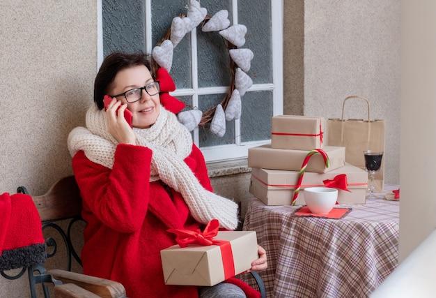 Женщина средних лет разговаривает по телефону накануне праздников рождества и нового года