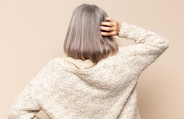 Женщина средних лет думает или сомневается, почесывает голову, чувствует недоумение и замешательство, вид сзади или сзади