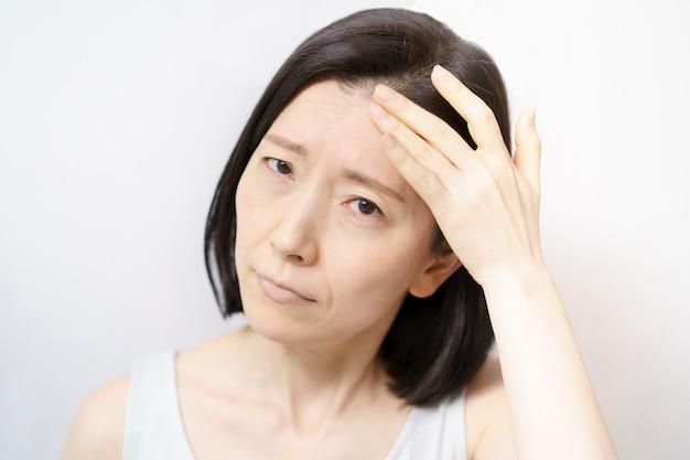 그녀의 얼굴을 만지고 피부 문제로 고통받는 중년 여성