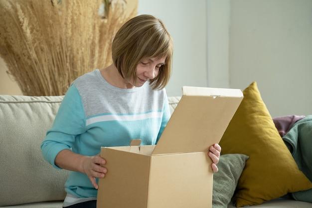 Женщина средних лет распаковывает картонную коробку, сидя на диване у себя дома
