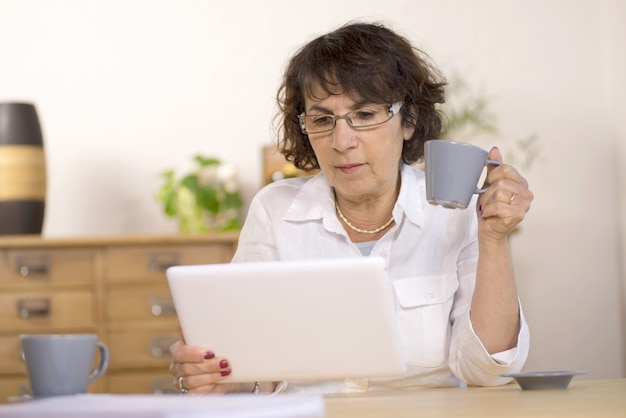 A middle-aged woman using a  computer tablet