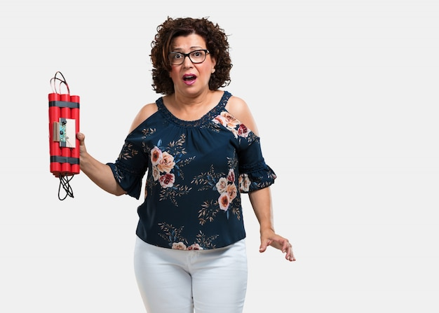 Middle aged woman very scared holding dynamite, bomb about to explode, terrorism concept