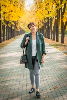 중년 여성이 가을 공원을 산책합니다. 오렌지 잎. 활동적인 라이프 스타일.