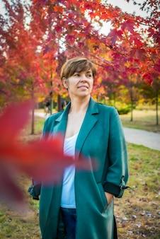 중년 여성이 가을 공원을 산책합니다. 주황색, 붉은 잎. 활동적인 라이프 스타일