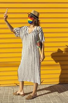 Женщина средних лет в шляпе, солнечных очках и защитной маске цвета радуги. lgtb на желтом фоне. концепция covid-19