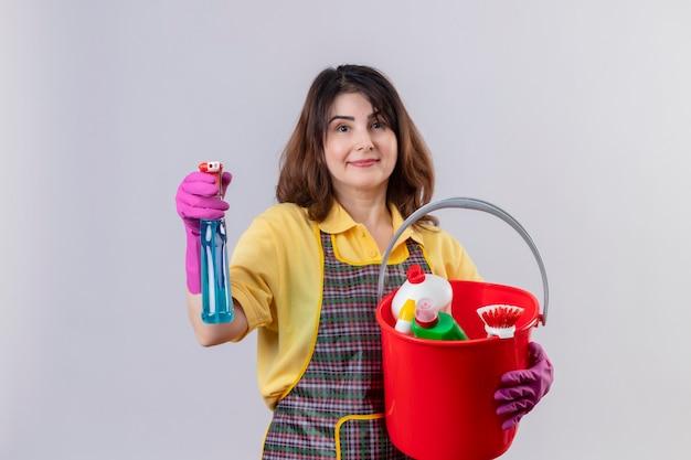 中年の女性がエプロンとゴム手袋をはめたバケツをクリーニングツールで保持し、白い壁の上にスプレーのポジティブで幸せな立っているをクリーニング