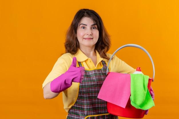 オレンジ色の背景の上に彼女の成功を喜んで元気よく肯定的で幸せな干し上げ拳を笑顔でカメラを見てクリーニングツールでバケツを保持しているエプロンとゴム手袋を着用して中年の女性