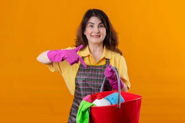 オレンジ色の壁3の上にポジティブで幸せな立っている笑顔を指して指しているクリーニングツールでバケツを保持しているエプロンとゴム手袋を身に着けている中年の女性