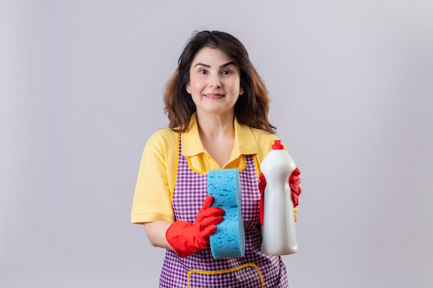 クリーニングスプレーとスポンジを保持しているエプロンとゴム手袋を着用して中年の女性