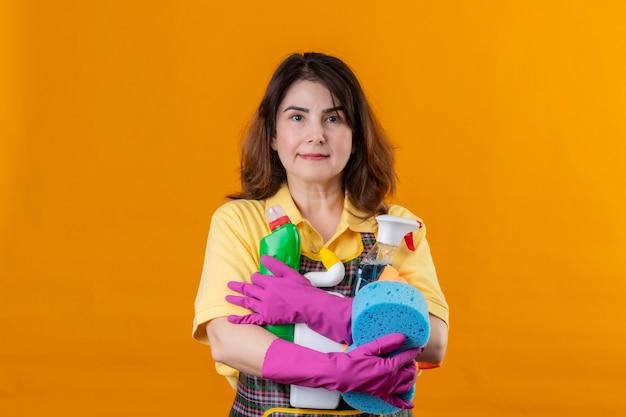 オレンジ色の壁の上に立っている顔に自信を持って真剣な表情でクリーニングツールを保持しているエプロンとゴム手袋を着用して中年の女性