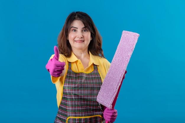 幸せそうな顔に笑みを浮かべてモップを保持しているエプロンとゴム手袋を着用して中年の女性