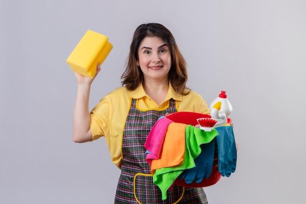 クリーニングツールと白い壁に陽気な肯定的で幸せな立っている笑顔のスポンジとバケツを保持しているエプロンを身に着けている中年の女性
