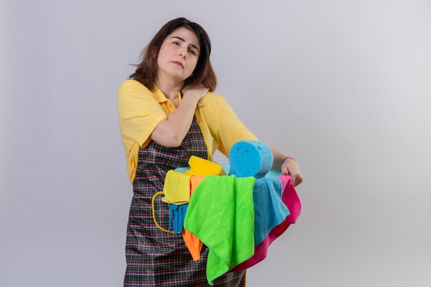 Middle aged woman wearing apron holding bucket with cleaning tools looking unwell touching her shoulder having pain standing over white wall