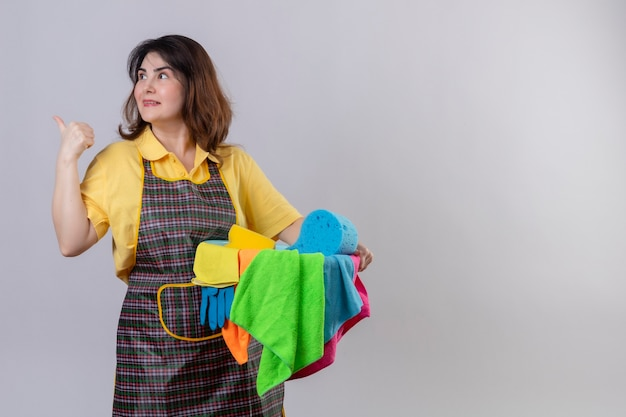 Middle aged woman wearing apron holding bucket with cleaning tools pointing to something behind smiling posotove and happy standing over white wall 2