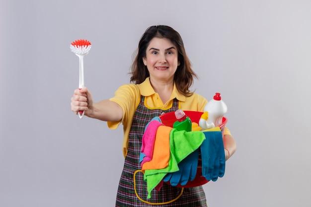Grembiule da portare della donna di mezza età che tiene la benna con gli strumenti di pulizia e la spazzola di sfregamento che sorride allegramente positivo e felice che sta sopra il muro bianco