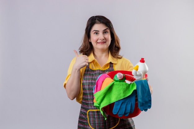白い壁2の上に立って親指を明るく陽気で幸せな親指を見せて笑ってクリーニングツール付きのエプロンホールディングバケツを着ている中年の女性