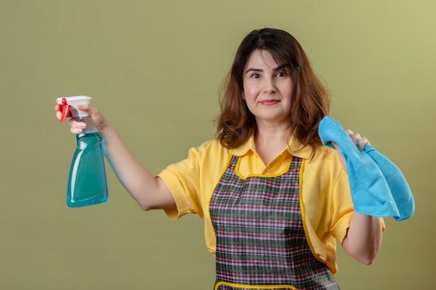 緑の壁の上にクリーニングスプレーと正と幸せの立っている笑顔の敷物を保持しているエプロンを着ている中年の女性