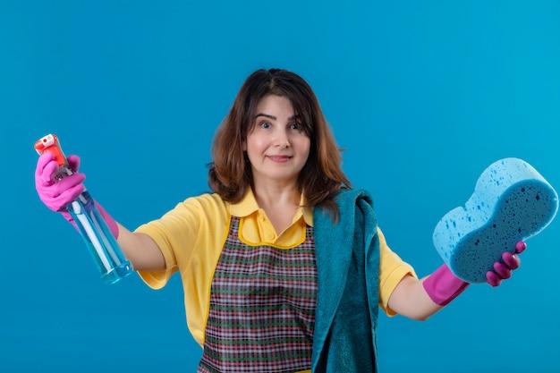 クリーニングスプレーとスポンジ笑顔を保持しているエプロンを着ている中年の女性