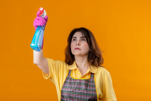 Middle aged woman wearing apron and rubber gloves cleaning using cleaning spray with serious face standing over orange wall
