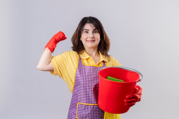 Middle aged woman wearing apron and rubber gloves holding bucket with cleaning tools looking at camera smiling cheerfully positive and happy raisning fist rejoicing her success standing over white bac