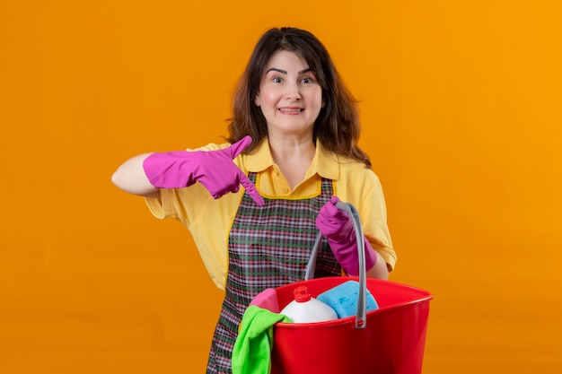 Middle aged woman wearing apron and rubber gloves holding bucket with cleaning tools pointing with finger to it smiling positive and happy standing over orange wall 3