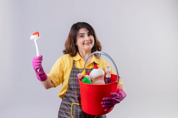 Grembiule da portare della donna di mezza età e guanti di gomma che tengono secchio con strumenti di pulizia e spazzola