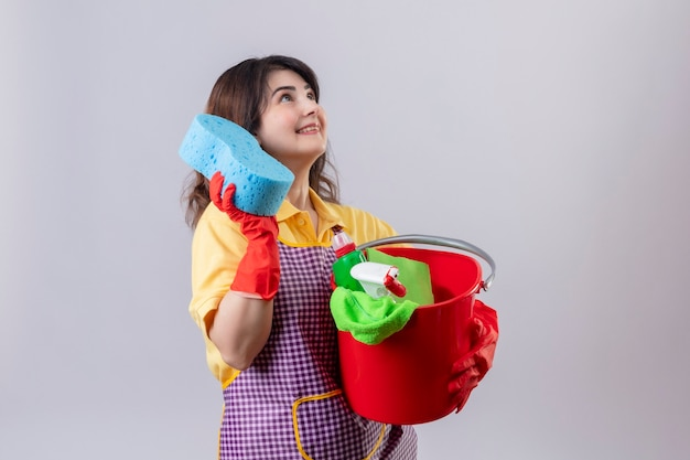 Middle aged woman wearing apron and rubber gloves holding bucket with cleaning tools and sponge