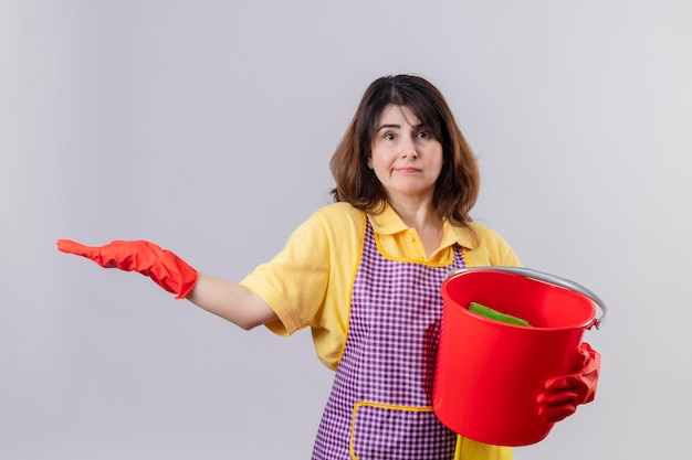 Middle aged woman wearing apron and rubber gloves holding bucket with cleaning tools