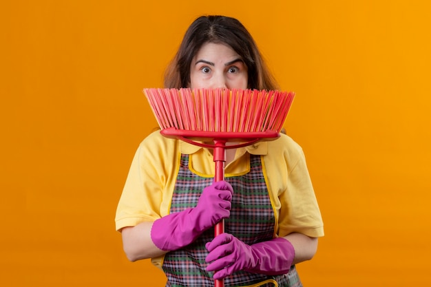 Middle aged woman wearing apron and rubber gloves holding mop hiding behind it looking surprised standing over orange wall