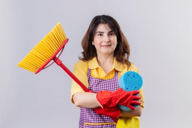 Grembiule da portare della donna di mezza età e guanti di gomma che stanno con i mop che tengono la spugna che sorride allegramente positivo e felice sopra il muro bianco