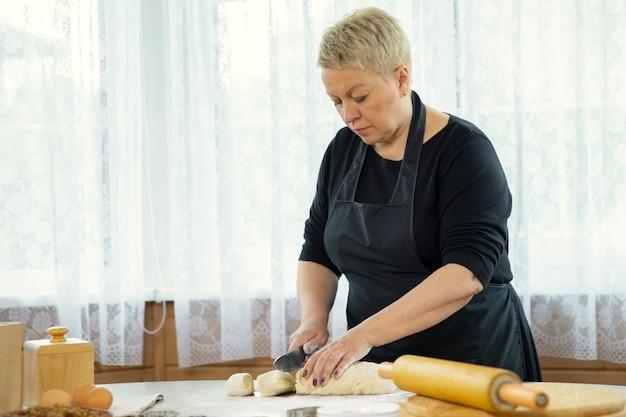 キッチンクラスの家族の伝統のコンセプトで自家製クッキーとペストリースライス生地を作る黒いエプロンを身に着けている中年の女性自家製のベーキングレッスンのコンセプト。ブログのコンセプト