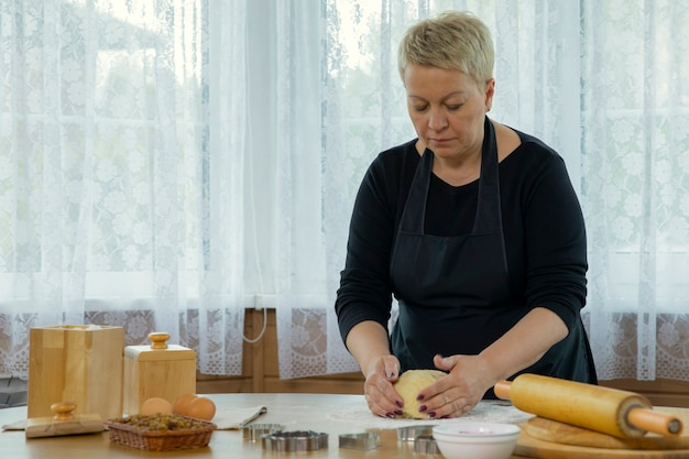 Middle-aged woman wearing black apron mashing dough for preparing gluten-free rolls in kitchen