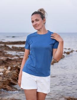 Женщина средних лет в синей футболке держит руку на плече и стоит на скале на закате