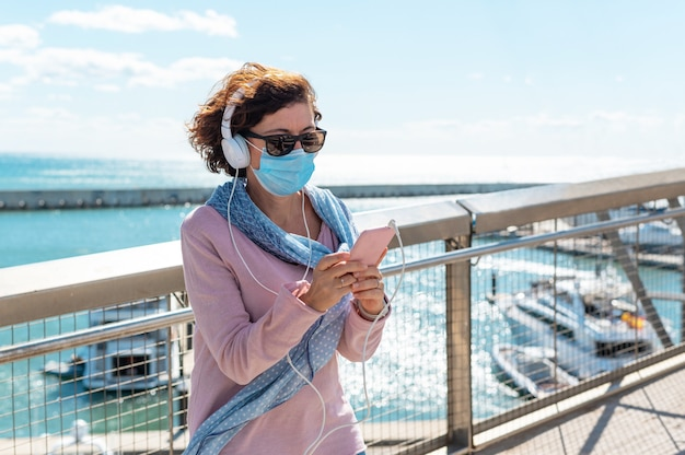 Middle-aged woman wearing a face mask standing on a bridge and listening to music