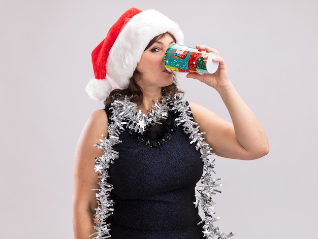 Middle-aged woman wearing santa hat and tinsel garland around neck looking at camera drinking coffee from plastic christmas cup isolated on white background