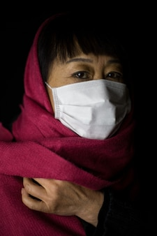 Middle-aged woman with a maroon hijab wearing a face mask on black
