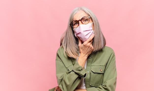 Женщина средних лет с широко открытыми глазами и ртом, положив руку на подбородок, ощущает неприятный шок, говорит что или вау