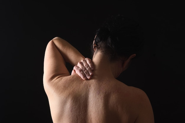 Middle-aged woman with pain in the neck on black background